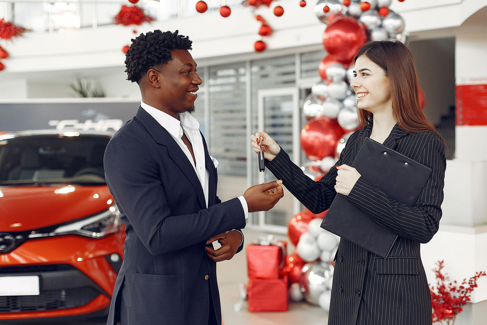 Car saleswoman handing consumer car keys