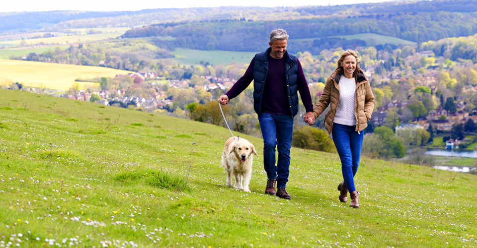 Middle aged couple taking a walk with dog