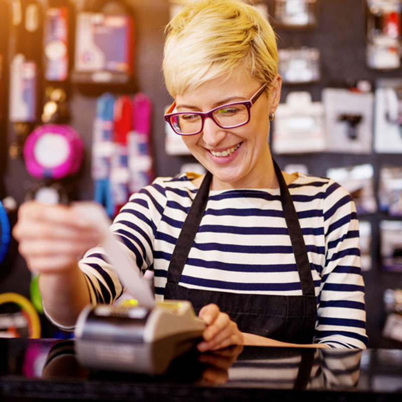 Woman printing off batch sales from credit card terminal