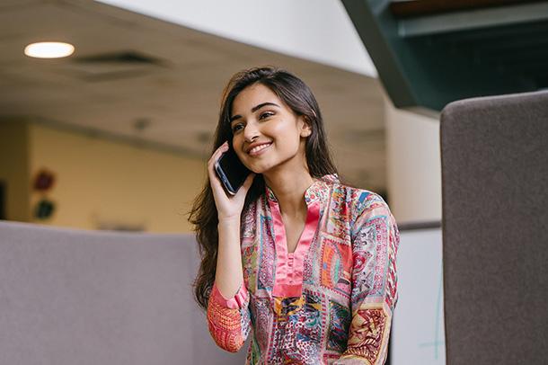 Smiling Woman in Floral Salwar Kameez Talking on Phone