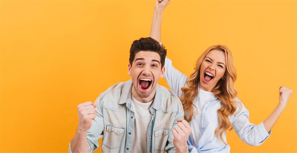 Two people celebrating in front of orange background