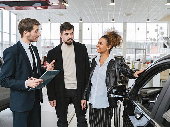 Car Salesman talking with husband and wife near a car