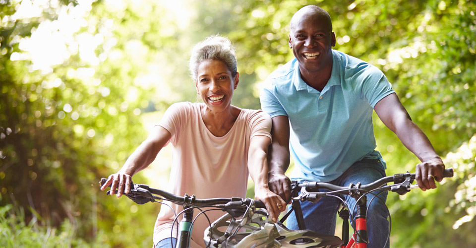 Middle aged couple riding their bikes down a rail trail smiling