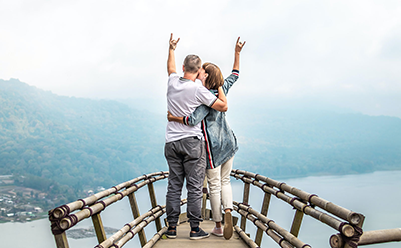 Retired couple on vacation standing on an overlook celebrating