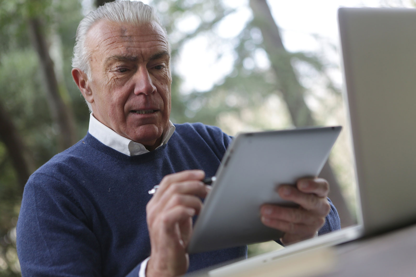 Senior male outside working on a tablet