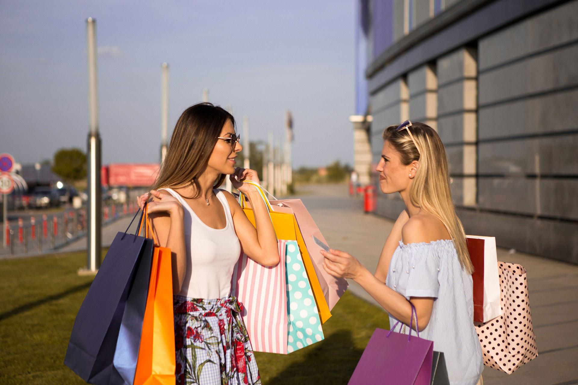 Two happy female friends shopping outside