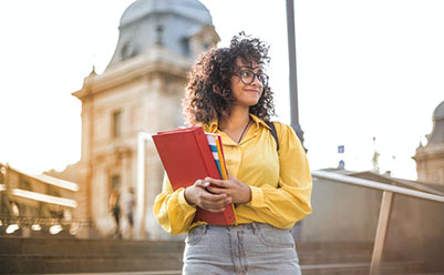 Female Student in Yellow Jacket Holding Red Book